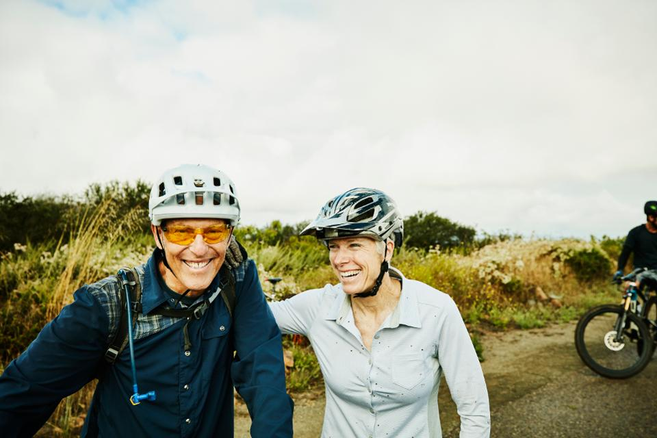 Smiling senior couple resting during mountain bike ride with friends