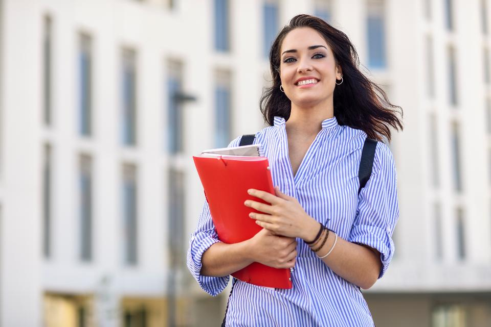 Portrait of smiling student with notebooks on campus