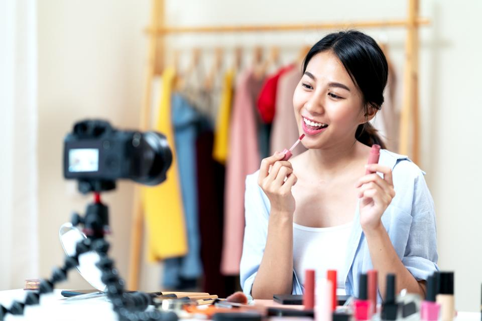 Portrait or headshot of attractive young asian influencer, beauty blogger, content creator or vlogger girl review make up looking at camera at home. Asian woman using internet for tutorial live video.