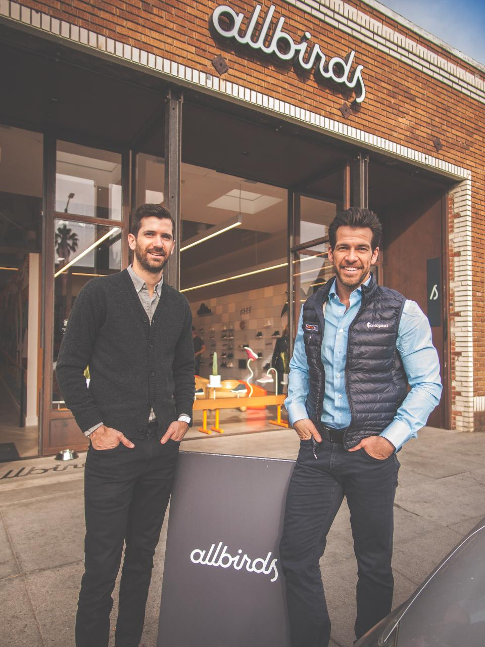 two smiling young men with hands jammed into front pocket of their jeans pose in front of Allbirds store.