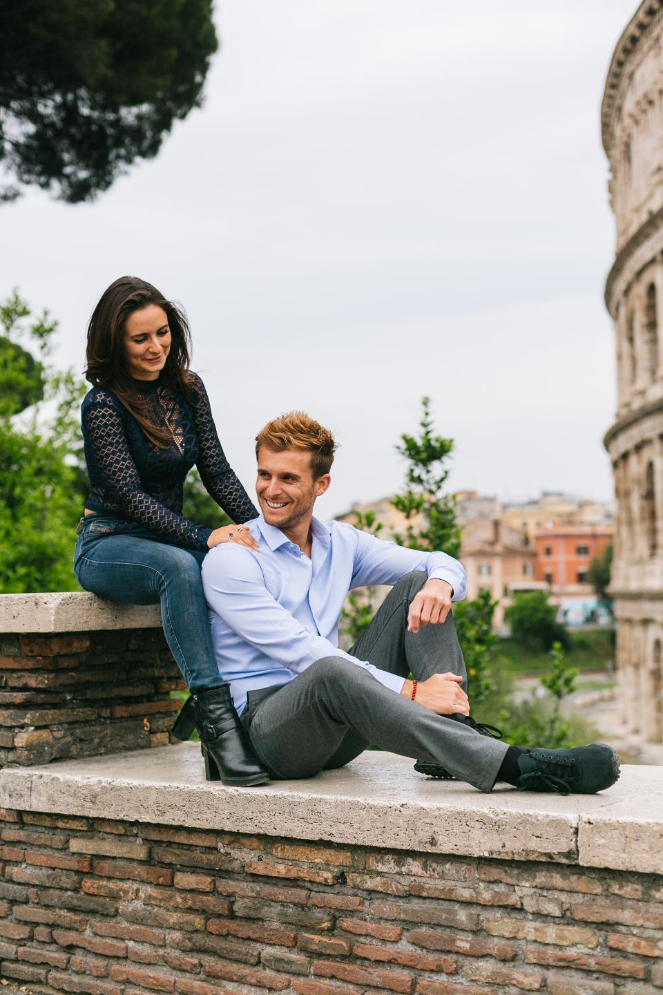 attractive man and woman entrepreneurs, couple sitting in front of colosseum in rome