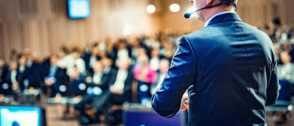 Rear view of a motivational coach giving a speech