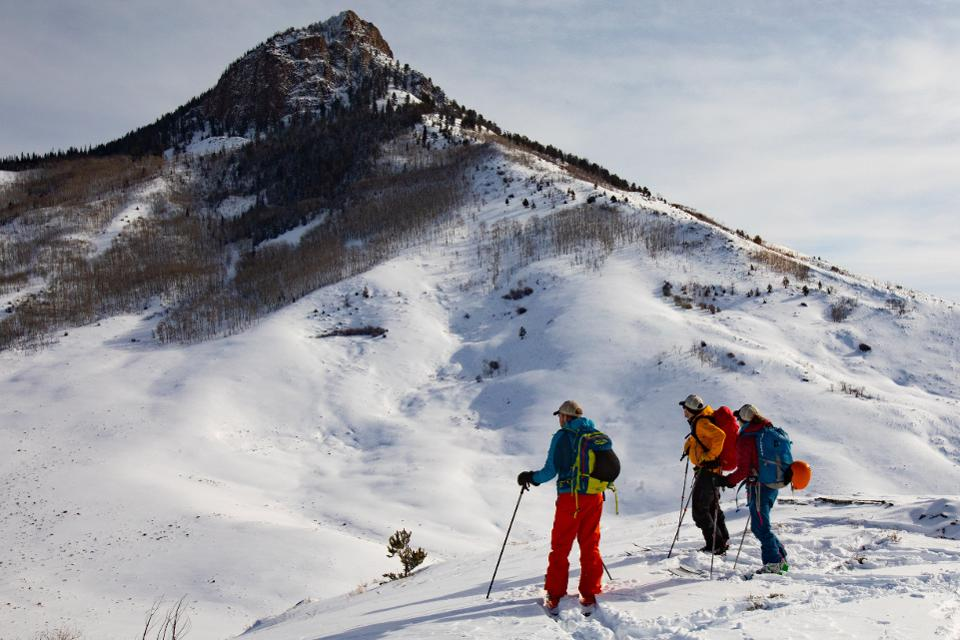 Three skiers at the summit of Bluebird Backcountry
